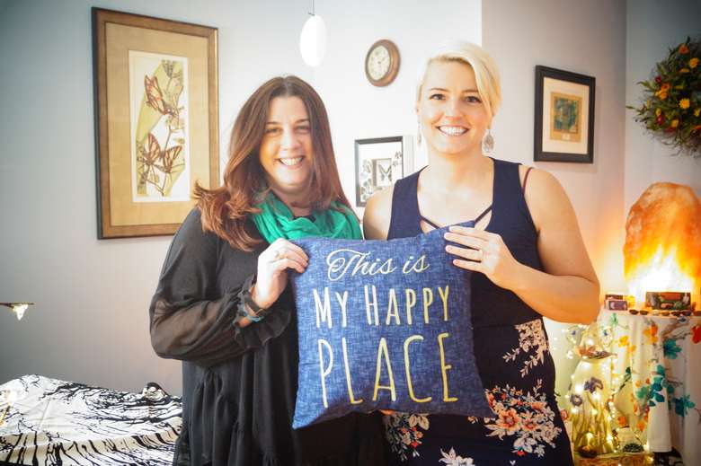 june stoddard-finemore and another woman posing with a pillow that says this is my happy place