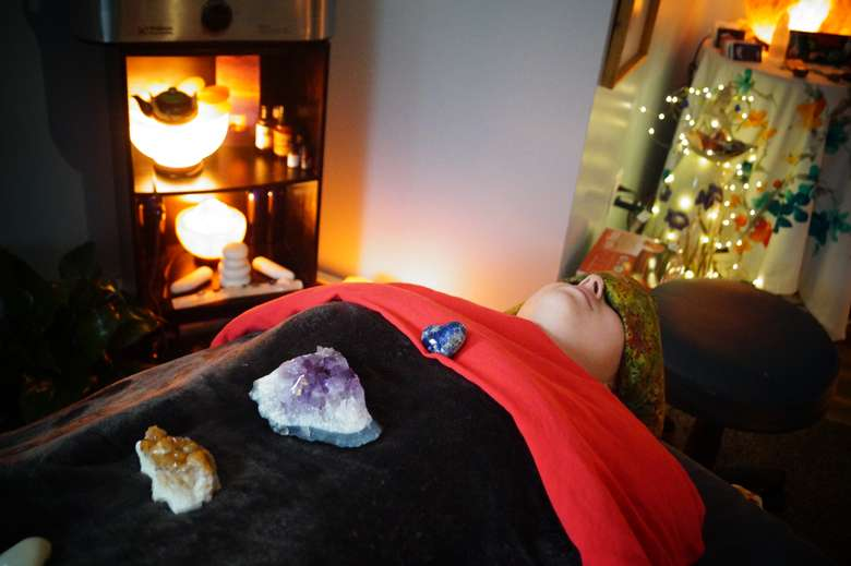 woman laying on a massage table under a blanket with chakra healing stones resting on her