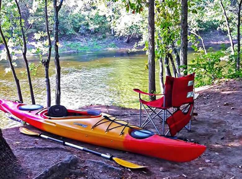 a colorful kayak next to a chair by the lake