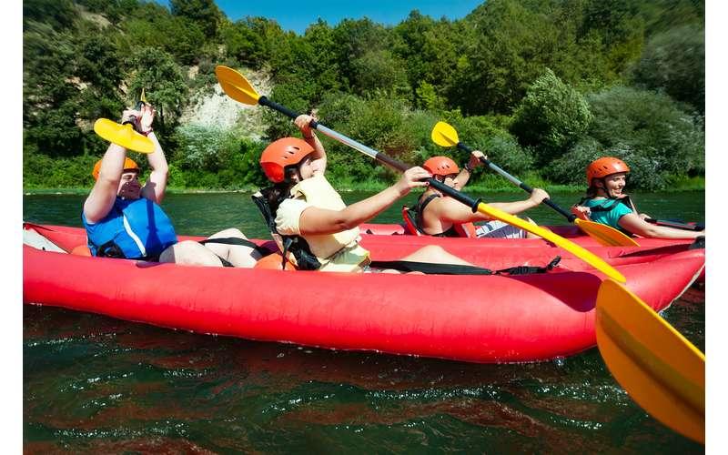 people kayaking on red kayaks with yellow paddles