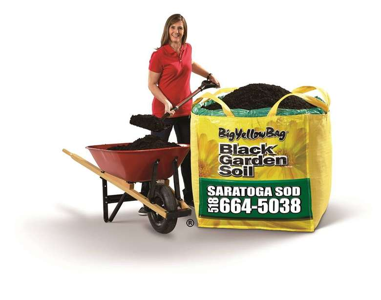 woman shoveling soil from a red wheelbarrow into a big yellow bag