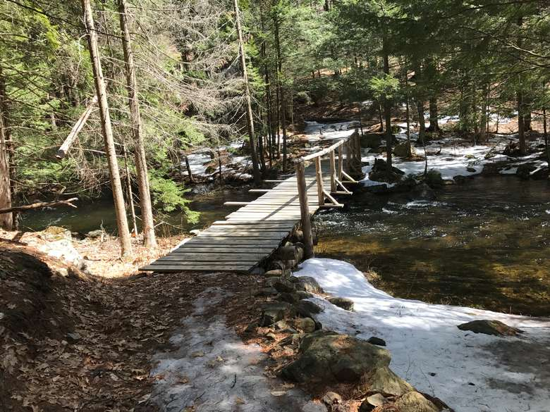a wooden bridge over a small waterfall