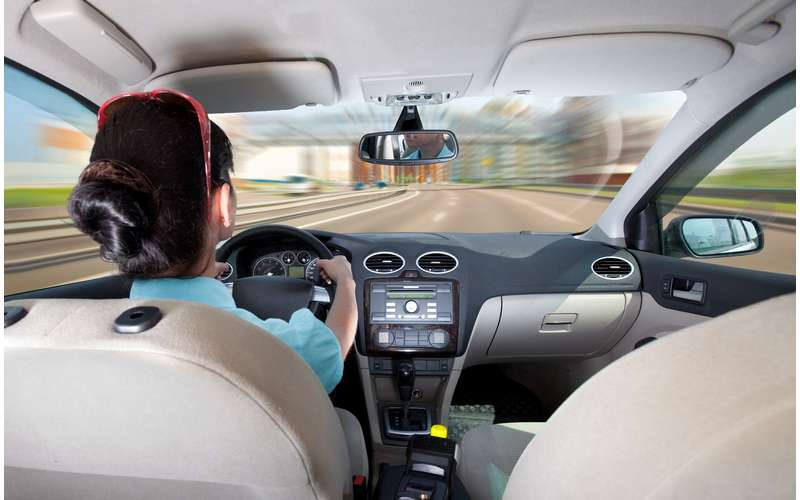 a back seat view of a woman driving a car down a road