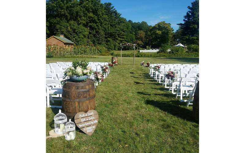 rows of white chairs on a grassy lawn in preparation for a wedding
