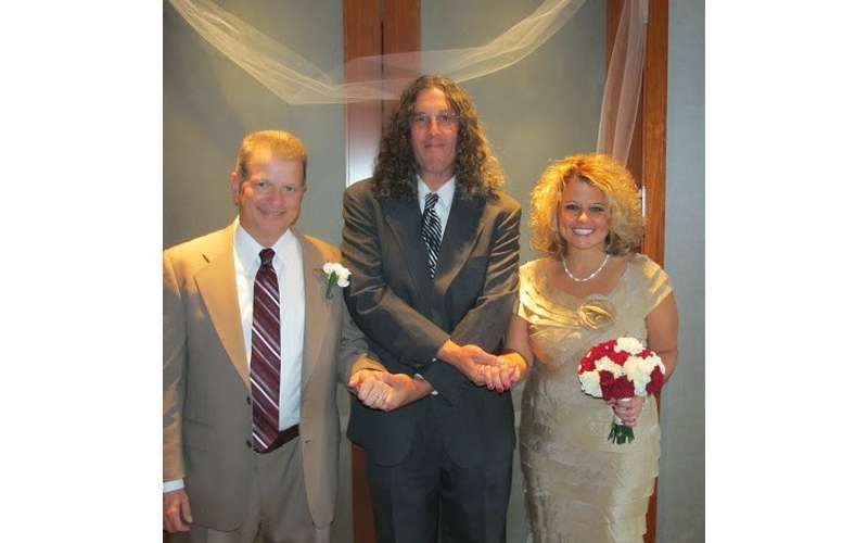 Reverend Ronald J. Hunt performing a ceremony with a happy couple.