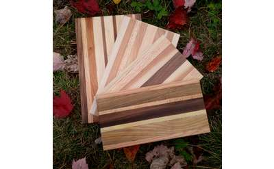four wooden cutting boards fanned out on a background of leaves and grass