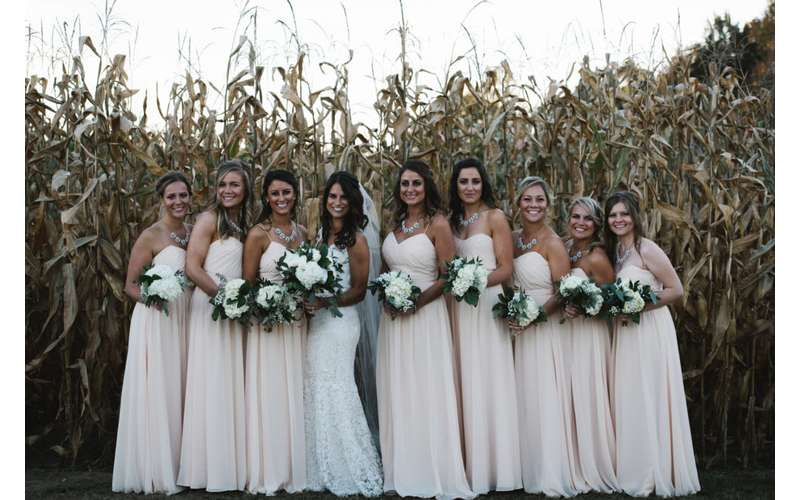 Line up by the wide open cornfield for a group photo.