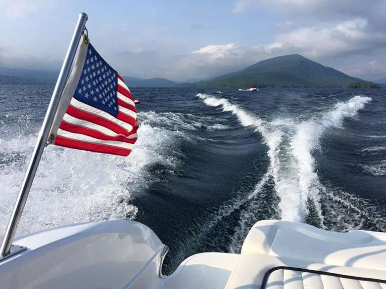 american flag on the back of a boat with the boat's wake in the background