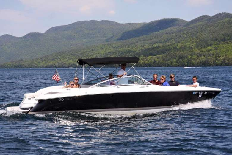 motorboat on lake george with mountains in the background
