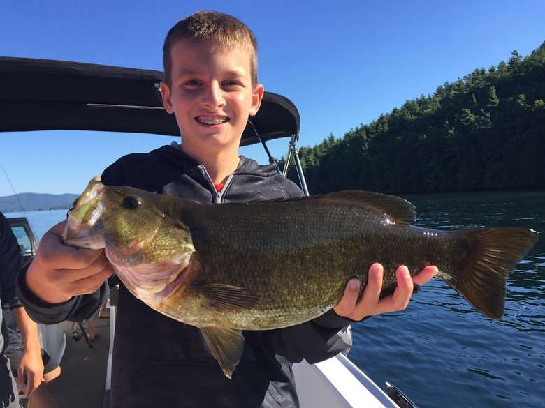 young boy holding a large bass