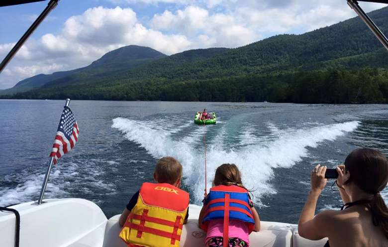 two kids and a woman watching people tubing on the back of a boat