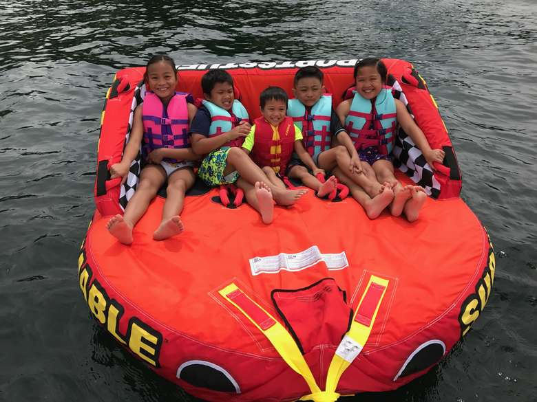 five kids in a tube getting ready to be pulled by a boat