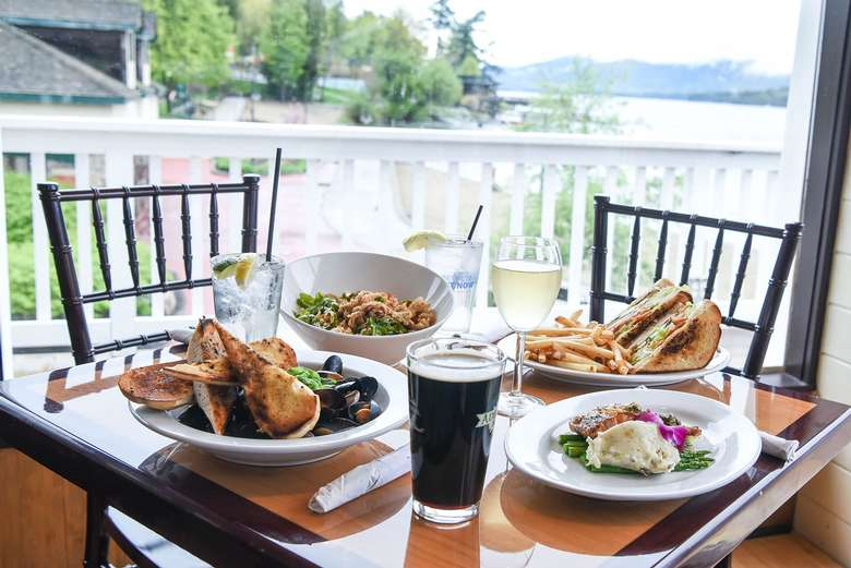 plates of food and drinks on a table at lake george beach club