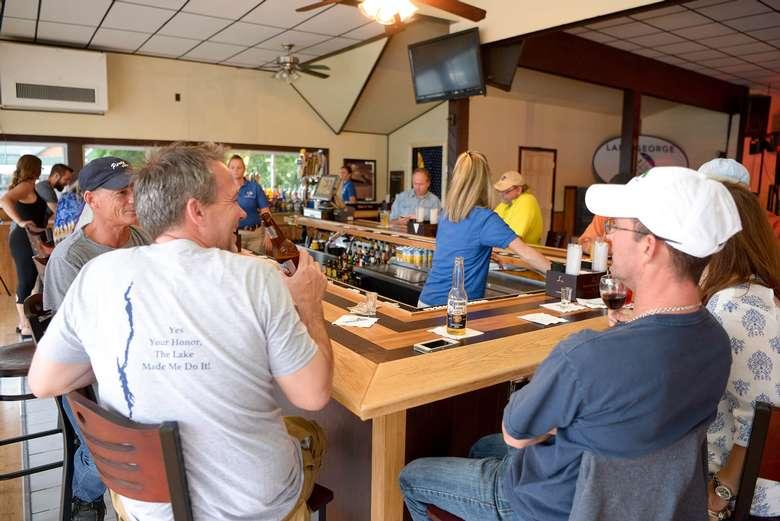 patrons sitting at the lake george beach club bar