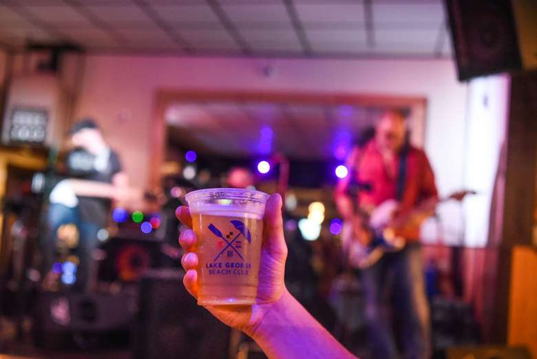 person holding a cup of beer while watching a musician perform inside at lake george beach club