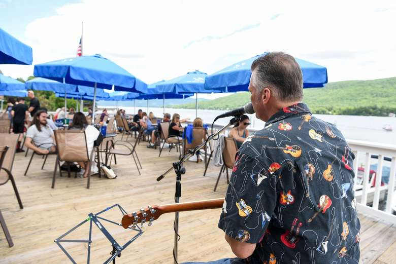 musician playing guitar on the patio at lake george beach club