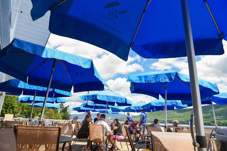tables with blue umbrellas on the patio at lake george beach club