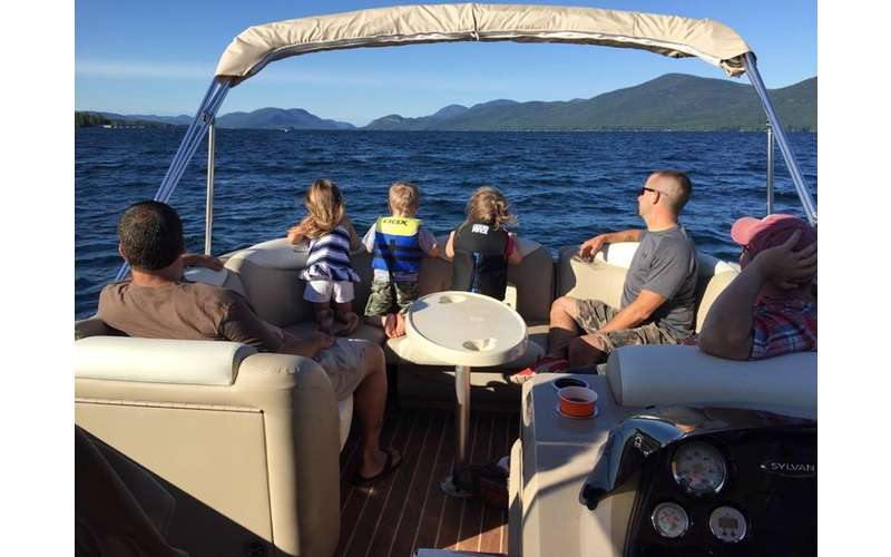 Family on a boat tour of Lake George with mountains in the background