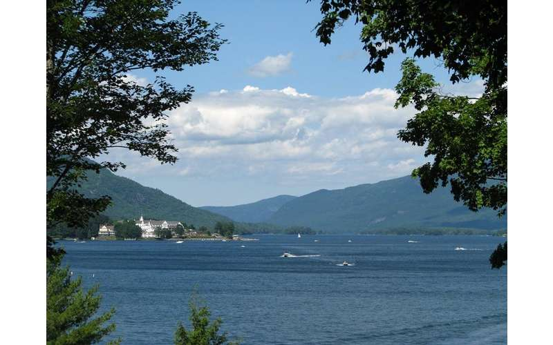 View of boats on Lake George with surrounding mountains in the background
