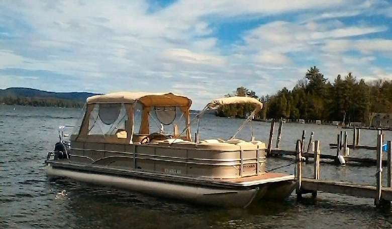 Side view of a tan pontoon boat