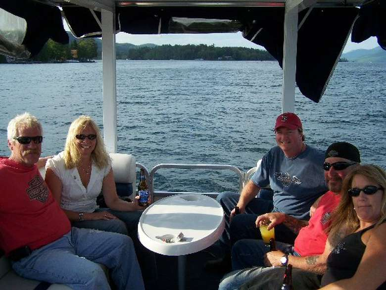 Five people getting a boat tour of Lake George