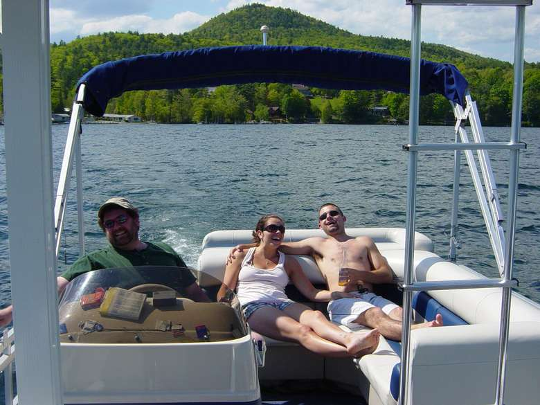 Two people relaxing in a boat while a third person drives