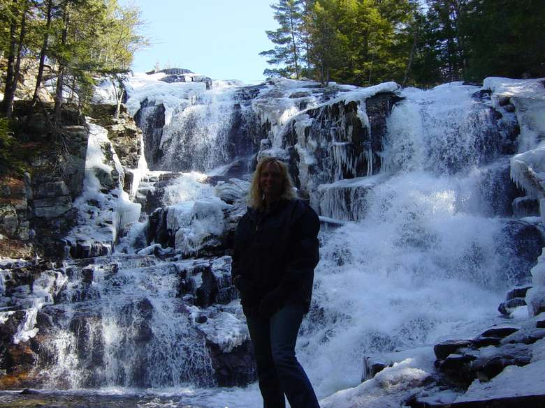 A woman standing in front of Shelving Rock Falls