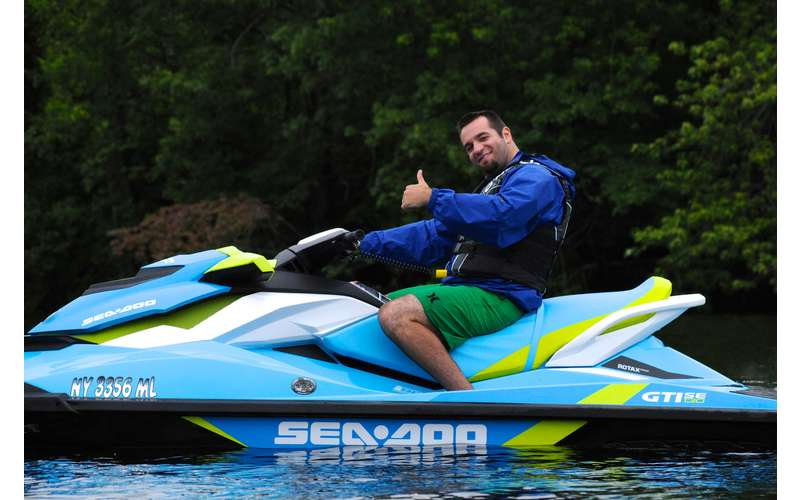 Man on a teal jetski giving a thumbs-up