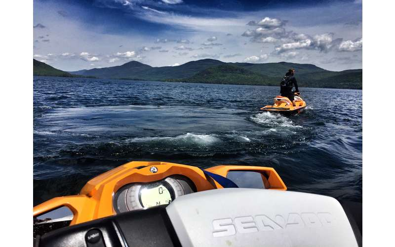 View of a person on an orange jetski from the driver's seat of another orange jetski