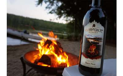 Bottle of red wine in front of a fire pit