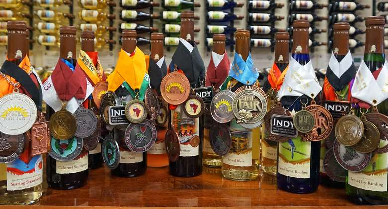 12 wine bottles with dozens of medals on them