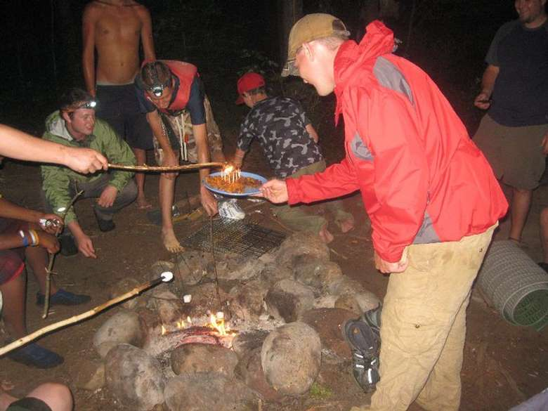 man holding a plate of s'mores supplies while other people roast marshmallows over a campfire