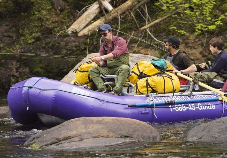 three men fishing in a whitewater raft with lots of gear