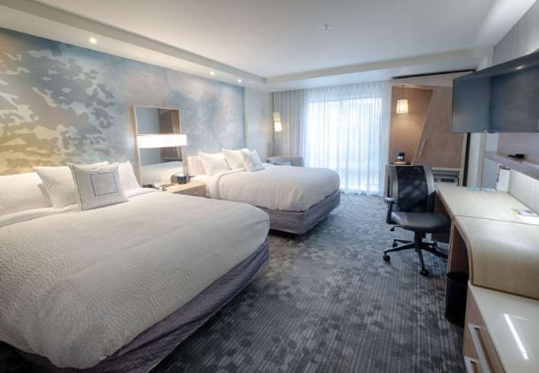 a spacious hotel bedroom with two beds and a workspace
