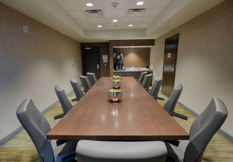 an enclosed meeting room space with a long table and chairs