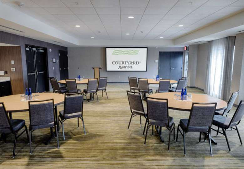 a large meeting space with round tables and a large screen in the back
