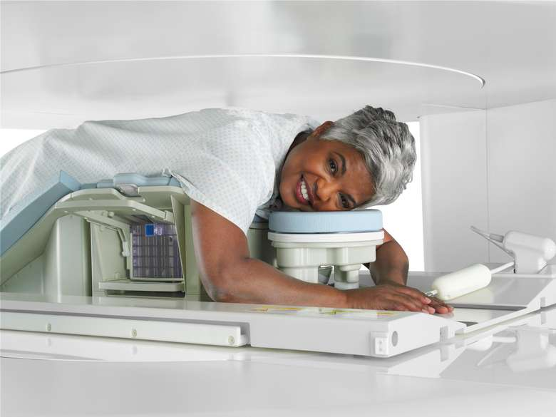 older woman smiling in MRI machine