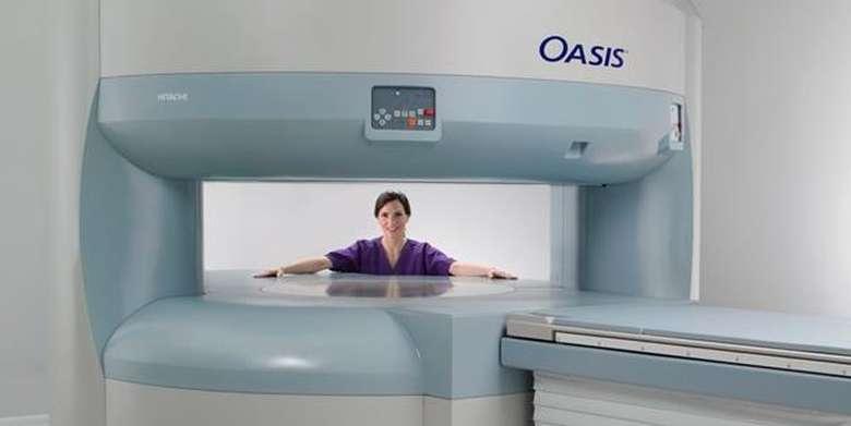 woman standing behind MRI machine