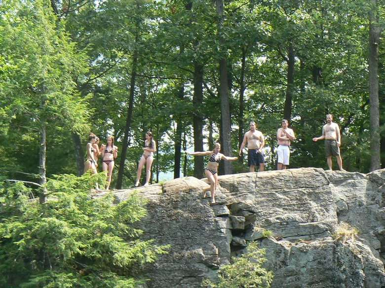 a group of people waiting to jump from a cliff into the water