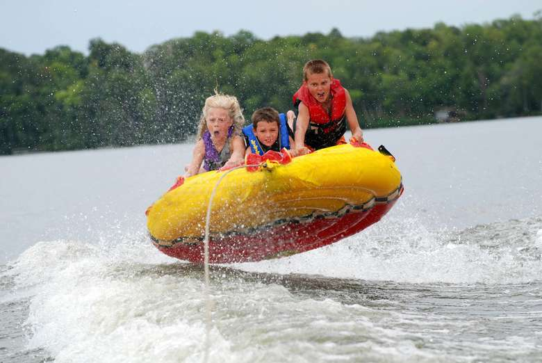 three kids on a large yellow tube being pulled across the water