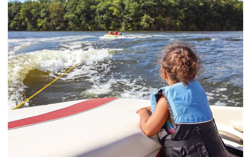 a girl looking at a group of people tubing from a motorboat