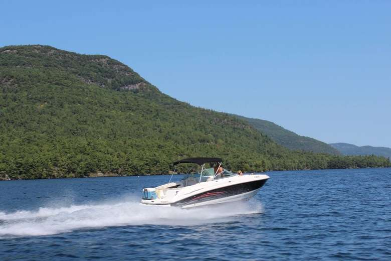 a large motorboat zooming across the waters of Lake George