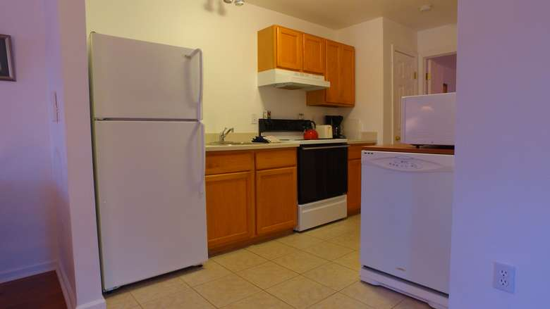 a kitchen space with a fridge, an oven, and a dishwasher