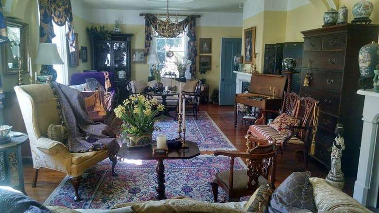 a large living room filled with all kinds of victorian era furniture and decor, such as chairs, desk, tables, and more