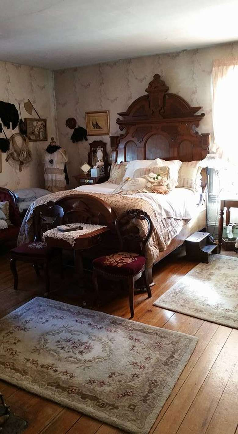 a queen bed from the 1840s in a bedroom with period clothing
