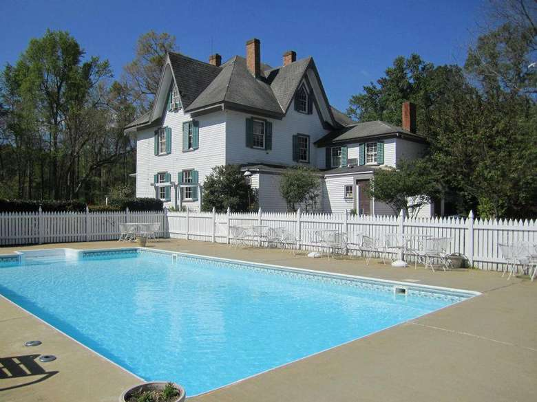 a clean, bright blue outdoor pool near a large white house