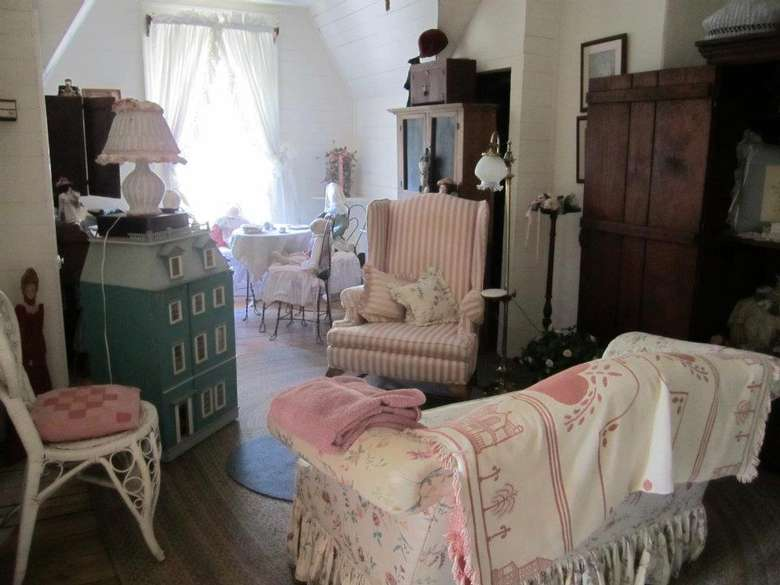 a green dollhouse, two chairs, and a small couch in a large room