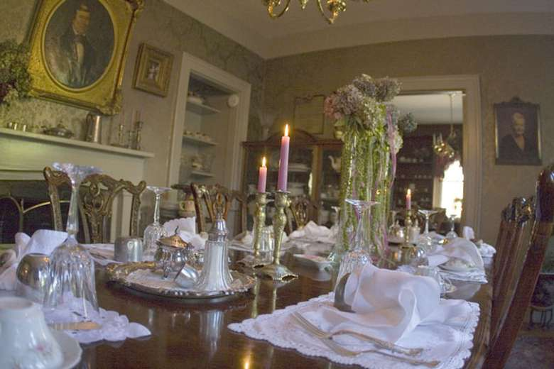 a dining table with lit candles and white placemats and glasses