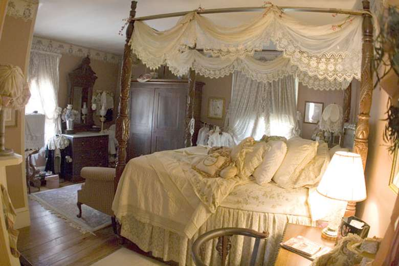 a large queen-size canopy bed from the victorian era with antique linens