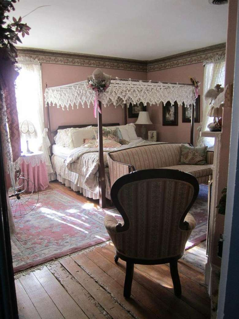 bedroom with antique linens, pink walls, and pink-themed carpet